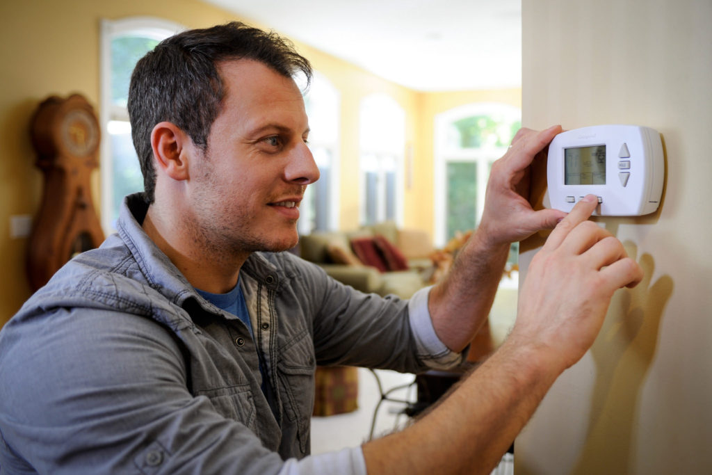 Man adjusts programmable thermostat