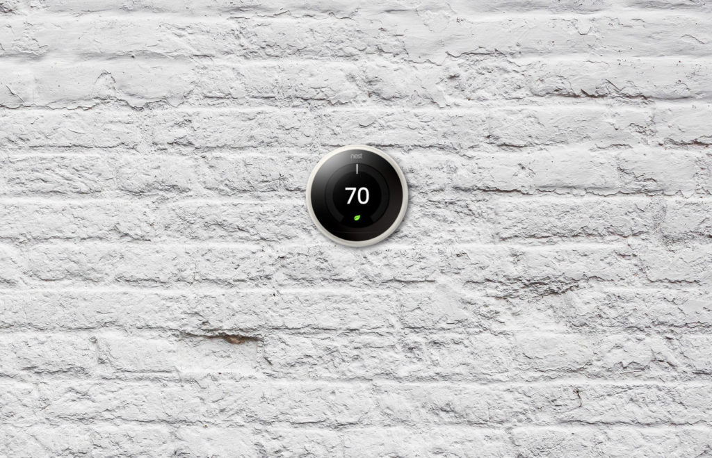 Nest Thermostat on white brick wall